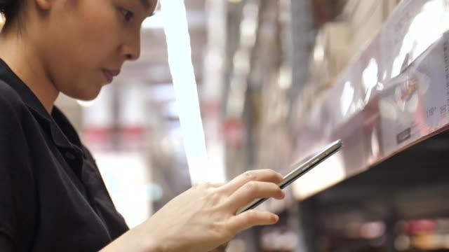 vídeos de stock, filmes e b-roll de lista de verificação de mulher fornece no tablet pc no armazém - catalogação