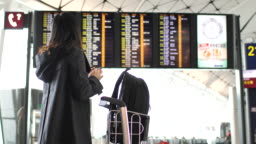 Woman Checking and looking flight at Arrival Departure Board