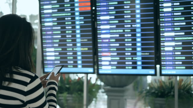 woman checking and looking flight at arrival departure board - digital signage stock videos and b-roll footage