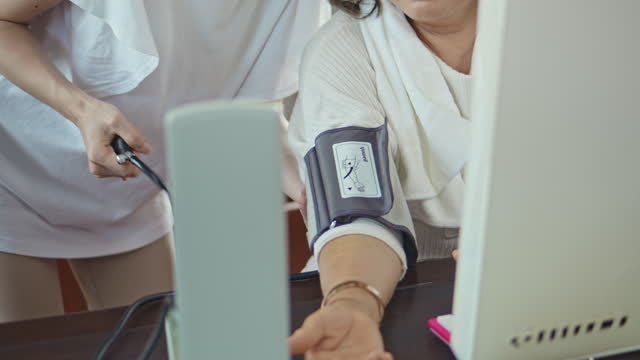 woman checking blood pressure gauge of mature woman at home - checked pattern stock videos & royalty-free footage