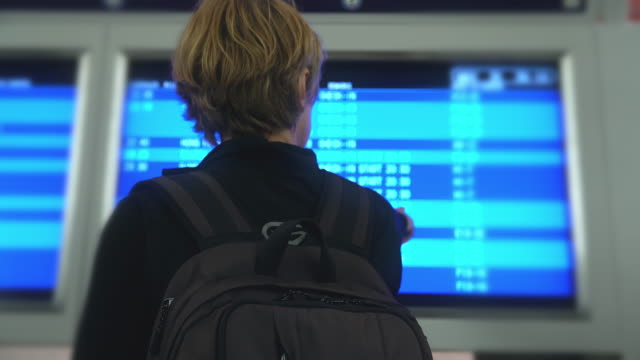 Woman checking departure board at the airport