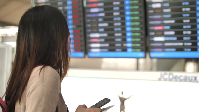 woman checking departure board with smart phone at the airport - unrecognisable person stock videos & royalty-free footage