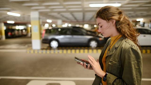 stockvideo's en b-roll-footage met vrouw die haar telefoon controleert terwijl het lopen in een parkeergarage - parking