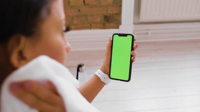 stockvideo's en b-roll-footage met vrouw die haar slimme telefoon tijdens oefening controleert - het zeer groene scherm van de chromasleutel - handdoek