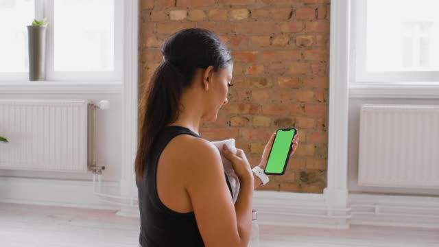 woman checking her smart phone during exercise - chroma key green screen - sweat stock videos & royalty-free footage