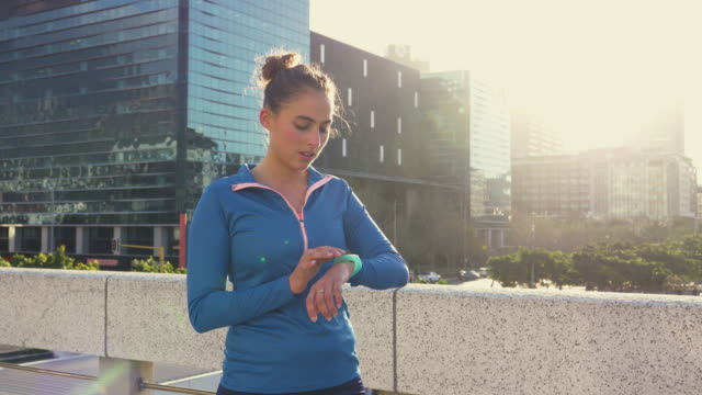 woman checking her smart watch while jogging in city - smart watch stock videos & royalty-free footage