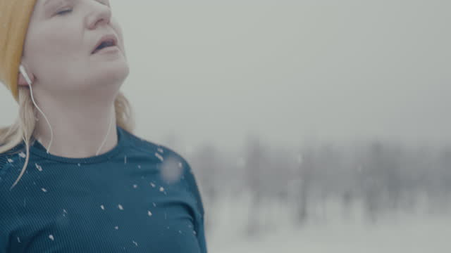 slo mo woman checking her smartwatch while jogging in the snow - athlete stock videos & royalty-free footage