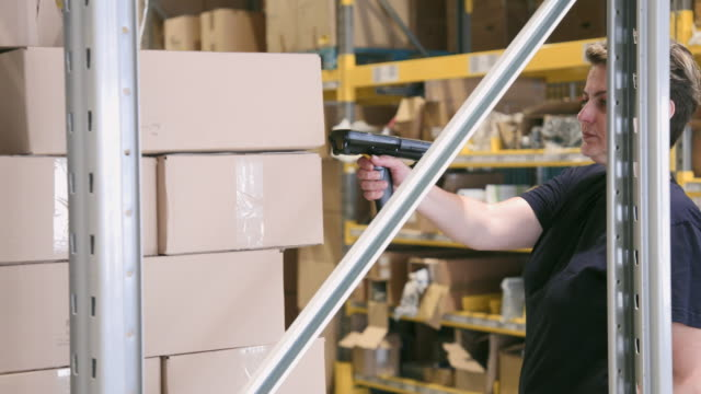 woman checking label and picking up cardboard box from rack - rack stock videos & royalty-free footage