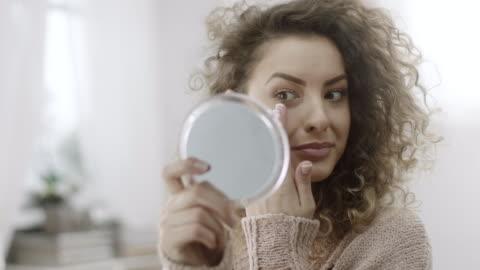 vídeos y material grabado en eventos de stock de mujer comprobando maquillaje en el espejo - smooth
