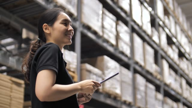 Woman checking on Digital tablet with cardboard boxes in distribution warehouse