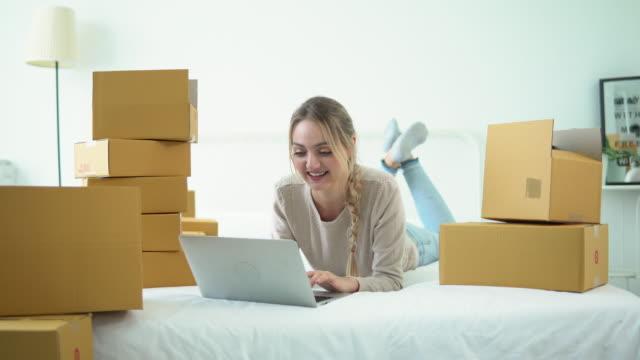 vídeos de stock e filmes b-roll de woman checking order on computer laptop on bed - agenda de telefones
