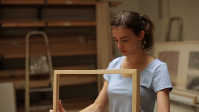 Woman checking picture frame in workshop