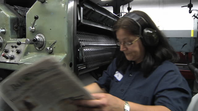 ms woman checking print quality of freshly printed edition and making adjustments at newspaper printing plant / powers, michigan, usa - one mature woman only stock videos & royalty-free footage