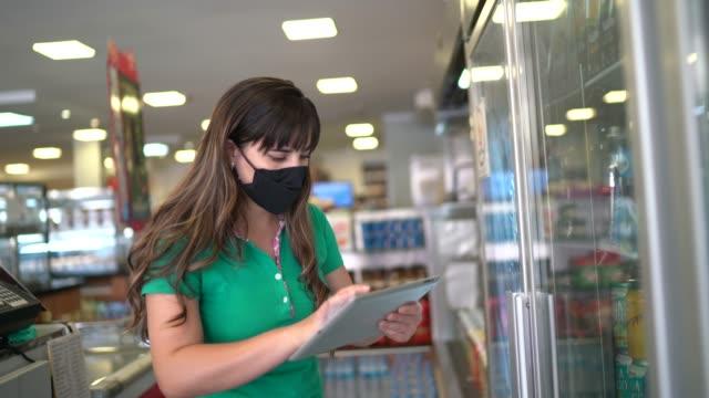 フェイスマスク付きデジタルタブレットを使用してパン屋やスーパーマーケットで製品をチェックする女性 - 操作する点の映像素材/bロール