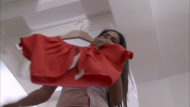 ms la woman checking red blouse in front of mirror in shop / brussels, belgium - clothes shop stock videos and b-roll footage