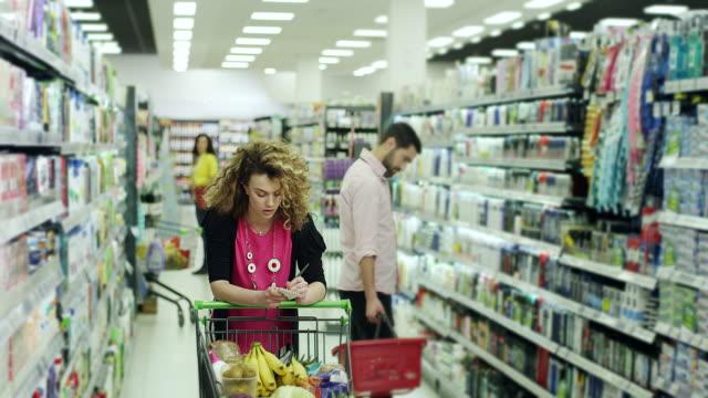 vídeos y material grabado en eventos de stock de mujer comprobar la lista de la compra en la tienda de comestibles - super slow motion