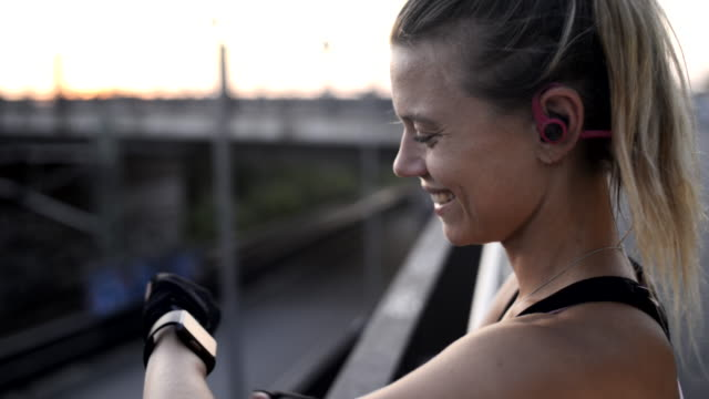 woman checking smartwatch after fitness workout. - kopfhörer stock-videos und b-roll-filmmaterial