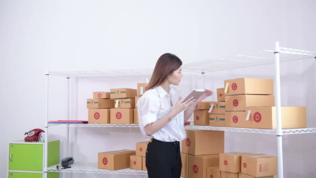 woman checking supplies in the warehouse - reading mail stock videos & royalty-free footage
