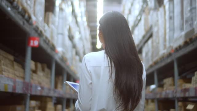 stockvideo's en b-roll-footage met vrouw controle van benodigdheden in het magazijn, slow motion - rug