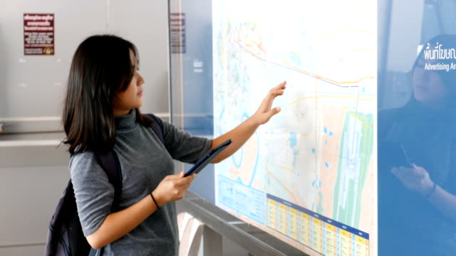 woman checking the map with tablet - window display stock videos and b-roll footage