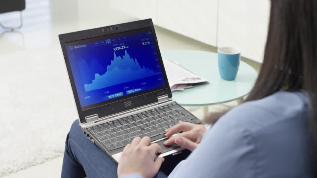 ds woman checking the statistics of a cryptocurrency value on her laptop - cryptocurrency stock videos & royalty-free footage