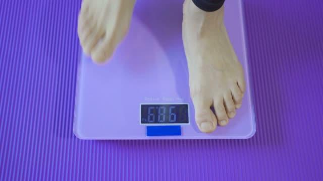 体重をチェックする女性 - 体重計点の映像素材/bロール