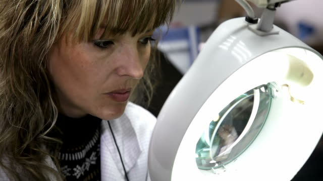 woman 小切手の回路基板を、拡大鏡 - 半導体点の映像素材/bロール