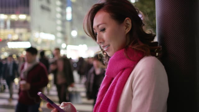 ms a woman checks her phone and looks around / tokyo, japan - scarf stock videos & royalty-free footage