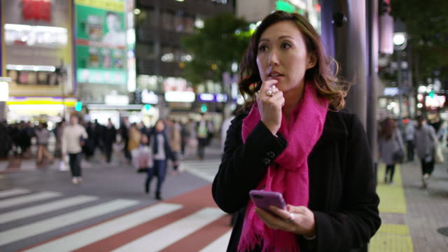 MS A woman checks her phone while waiting in Shibuya / Tokyo, Japan