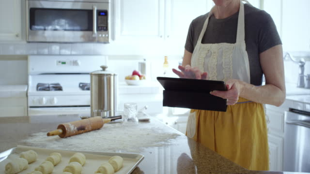 woman checks her tablet for dinner roll recipe - recipe stock videos & royalty-free footage