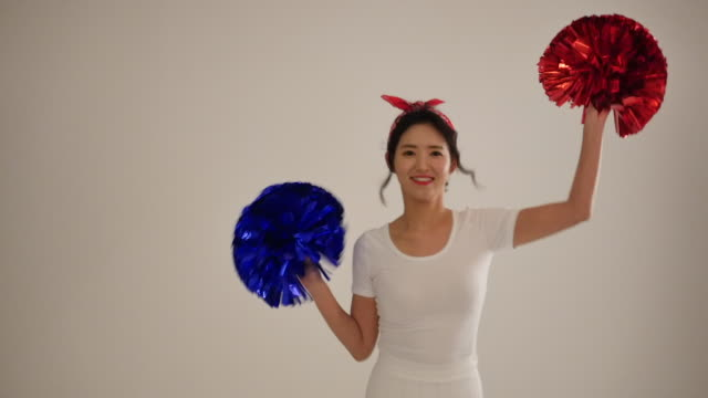 woman cheering for her team with red and blue pom-poms - pom pom stock videos & royalty-free footage