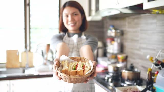 vídeos y material grabado en eventos de stock de mujer chef servir un sándwich sosteniendo y mostrando en frente - pequeño