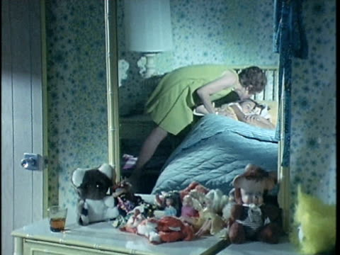 vidéos et rushes de 1971 montage woman chickening on children in bed, los angeles, california, usa, audio   - caresser