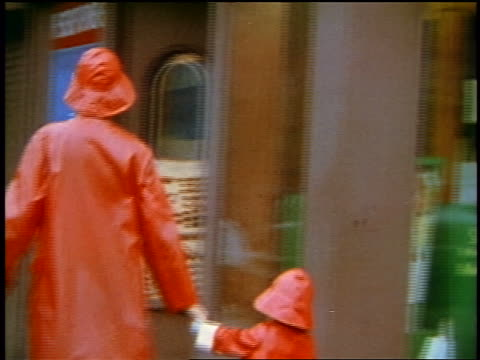 1957 rear view woman + child in matching red raincoats walking hand in hand on city sidewalk - waterproof clothing stock videos & royalty-free footage