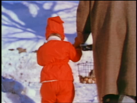 1957 rear view woman + child in red snowsuit walking hand in hand in snow / feature - 1957 stock-videos und b-roll-filmmaterial
