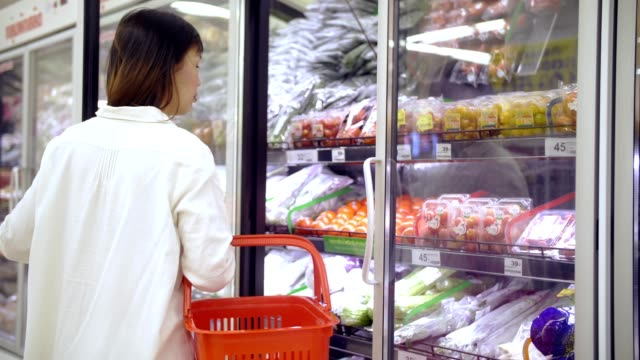 woman choose a vegetable in minimarket - tomato stock videos and b-roll footage
