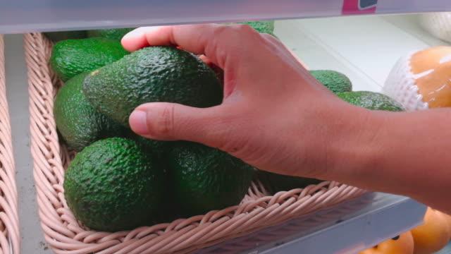woman choose avocados in supermarket shot by smart phone - choosing stock videos & royalty-free footage