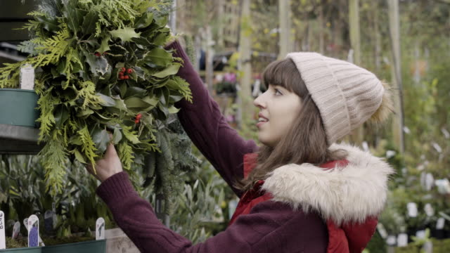woman chooses a christmas wreath at christmas market. - リース点の映像素材/bロール