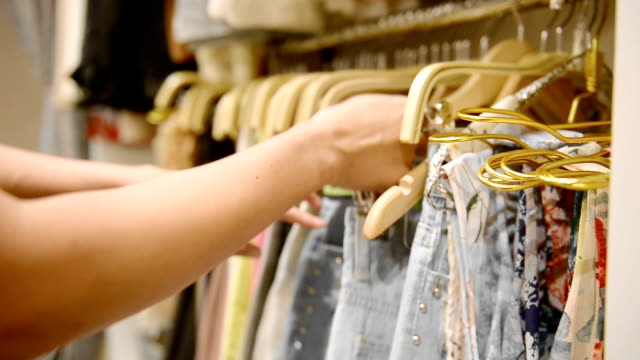 A Woman Chooses A Dress In A Clothing Retail Store. Close Up Hands.