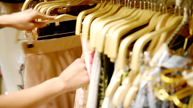 a woman chooses a dress in a clothing retail store. close up hands. - dress stock videos and b-roll footage