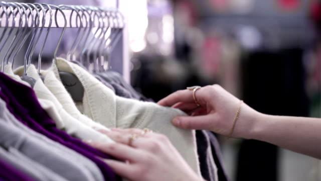 Frau wählt Kleider in Bekleidungsgeschäft