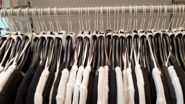 vidéos et rushes de la femme choisit des vêtements dans le centre commercial - jeans