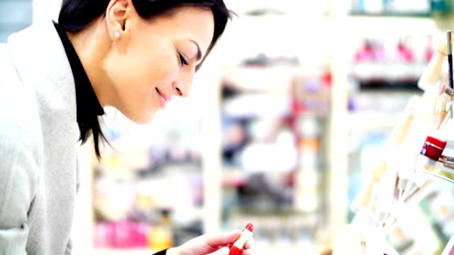 woman choosing a lipstick at beauty store. - warm clothing stock videos & royalty-free footage