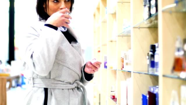 vídeos de stock, filmes e b-roll de mulher escolher um perfume. - perfumado