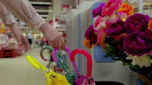 donna scegliendo un ombrello in mercery supermercato - ombrello video stock e b–roll