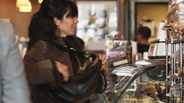 vídeos de stock e filmes b-roll de woman choosing and buying a baked good at a bakery - cristaleira
