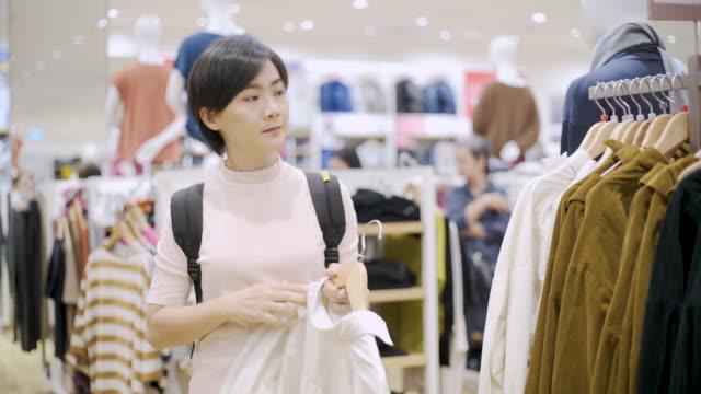 stockvideo's en b-roll-footage met vrouw kiezen kleren en op zoek naar spiegel in kledingwinkel - boetiek