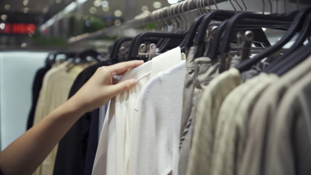 woman choosing clothes in hanging rail in clothes shop - clothes rail stock videos & royalty-free footage