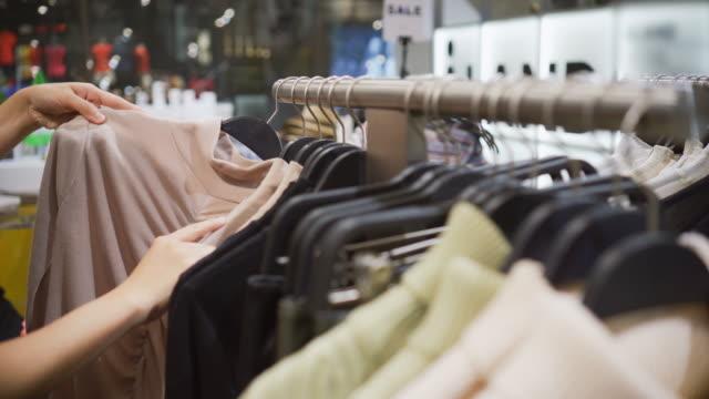 vidéos et rushes de femme choisissant des vêtements dans le rail suspendu dans le magasin de vêtements - boutique