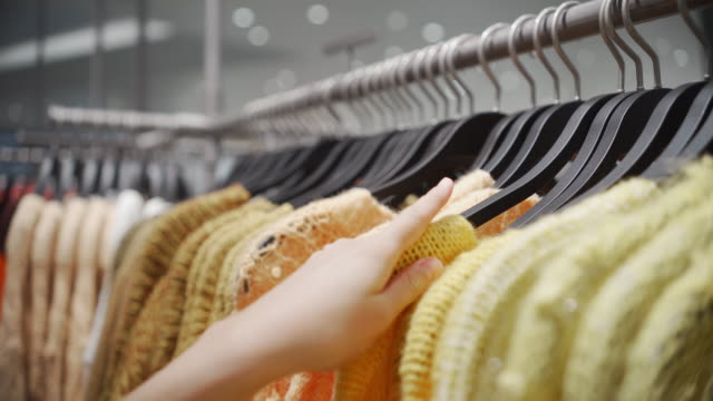 woman choosing clothes in hanging rail in clothes shop - department store stock videos & royalty-free footage